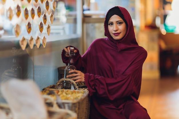 Arabische jonge moslimvrouw zit in een café