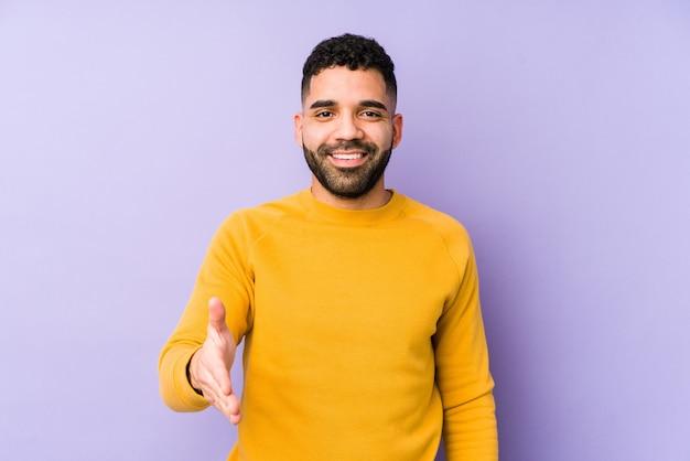 Arabische jongeman gemengd ras geïsoleerd uitrekkende hand in groetgebaar.