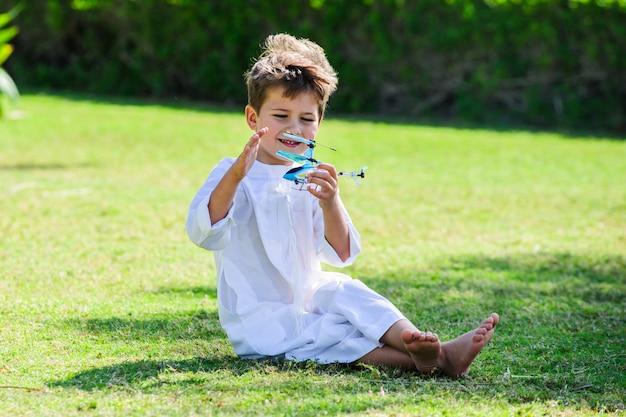 Arabische jongen speelt met speelgoed helikopter.