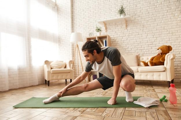 Arabische kerel doet stretching oefening op gymtapijt.