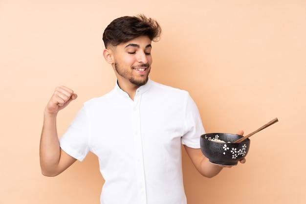 Arabische knappe man die op beige muur wordt geïsoleerd die een overwinning viert terwijl hij een kom noedels met eetstokjes vasthoudt