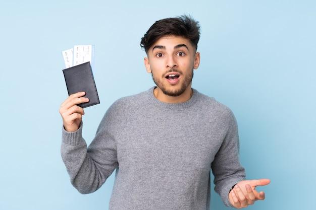 Arabische knappe man geïsoleerd op blauwe muur gelukkig in vakantie met paspoort en vliegtickets