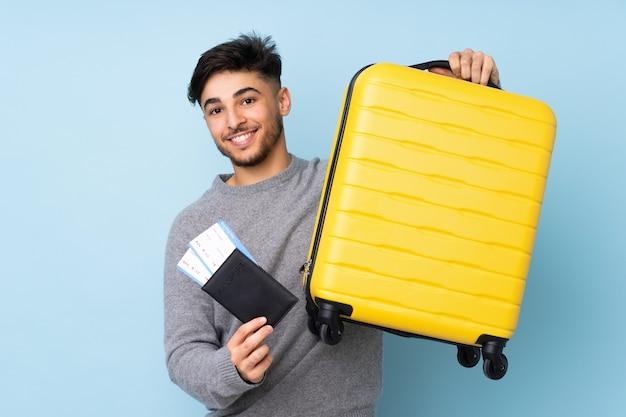 Arabische knappe man geïsoleerd op blauwe muur in vakantie met koffer en paspoort