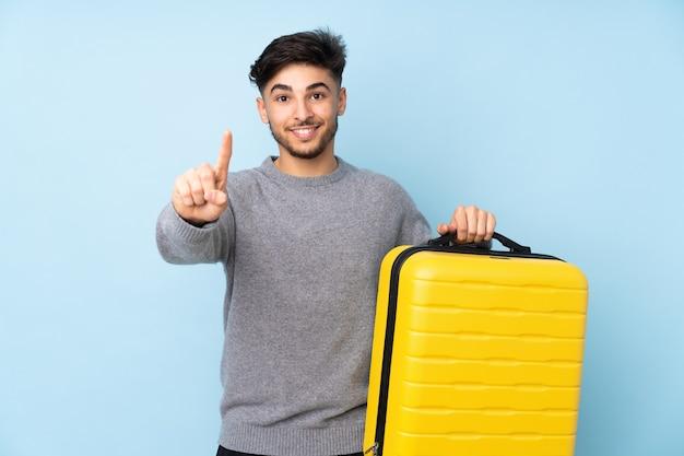 Arabische knappe man geïsoleerd op blauwe muur in vakantie met reiskoffer en een tellen
