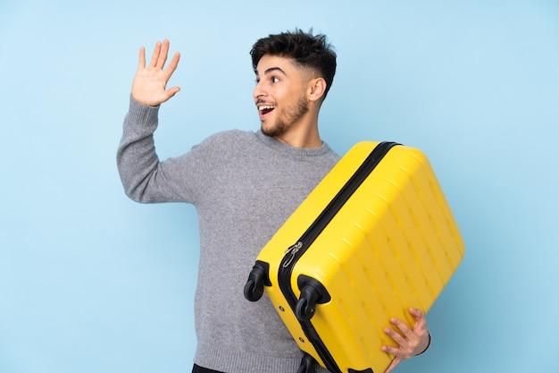 Arabische knappe man geïsoleerd op blauwe muur in vakantie met reiskoffer en groeten