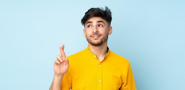 Arabische knappe man over geïsoleerd met vingers die kruisen en het beste wensen