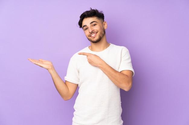 Arabische knappe man over geïsoleerde muur die denkbeeldige copyspace op de palm houdt om een advertentie in te voegen