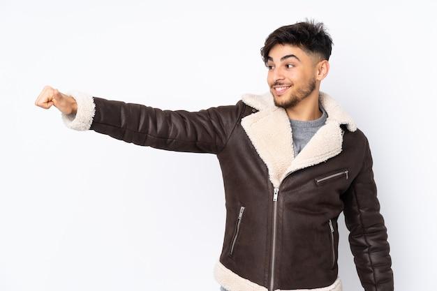 Arabische knappe man over geïsoleerde muur die een duim omhoog gebaar geeft