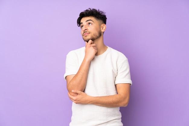 Arabische knappe man over geïsoleerde muur die een idee denkt terwijl hij omhoog kijkt