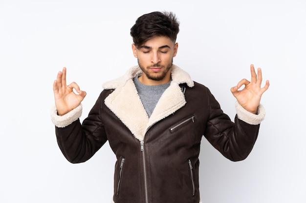 Arabische knappe man over geïsoleerde muur in zen pose