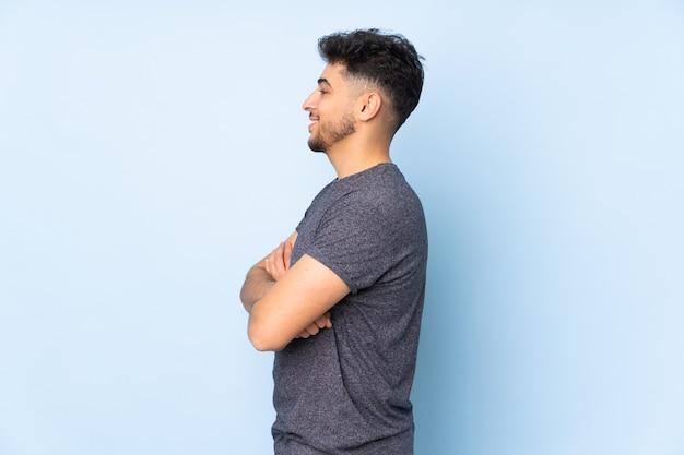 Arabische knappe man over geïsoleerde muur in zijpositie