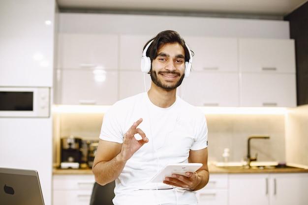 Arabische man die online webinar kijkt, zittend in een keuken met een tablet en geniet van afstandsonderwijs