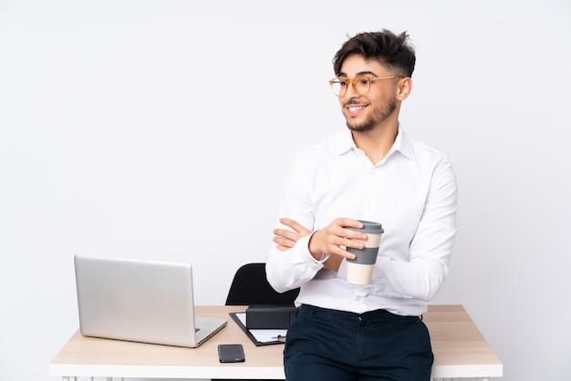 Arabische man in een kantoor geïsoleerd op wit blij en lachend