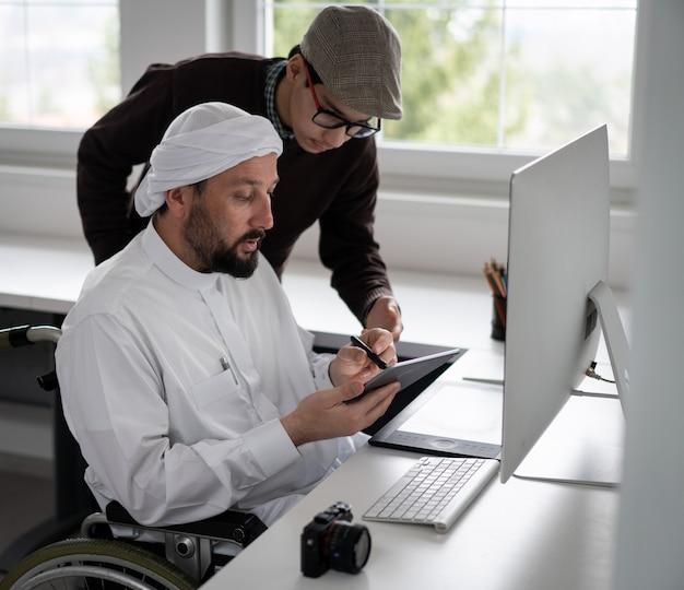 Arabische man in rolstoel bij bureau met computer