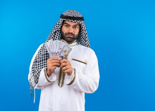 Arabische man in traditionele kleding die contant geld toont met zelfverzekerde ernstige uitdrukking die zich over blauwe muur bevindt