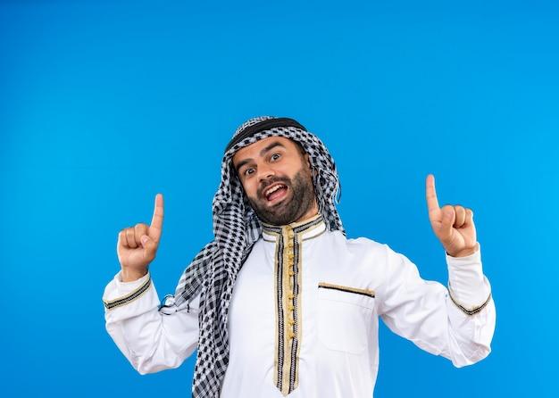 Arabische man in traditionele kleding die met omhoog vingers wijst die vrolijk glimlacht zich over blauwe muur bevindt