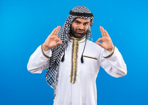 Arabische man in traditionele kleding die oo-tekens maakt met beide handen die zelfverzekerd over de blauwe muur kijken