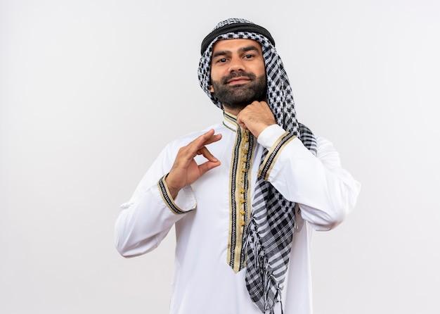 Arabische man in traditionele kleding die zijn kraag bevestigt die zich over witte muur zelfverzekerd bevindt