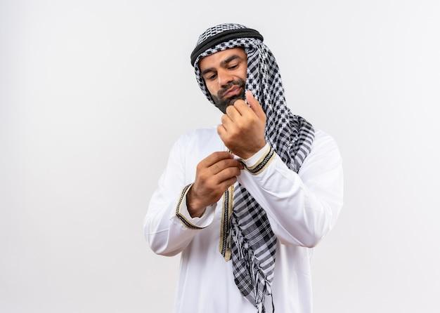 Arabische man in traditionele kleding die zijn manchetknoop met zelfverzekerde blik bevestigt die over witte muur staat