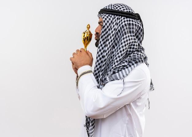 Arabische man in traditionele kleding die zijn trofee kust die zijwaarts over witte muur staat