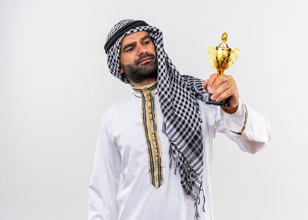 Arabische man in traditionele kleding die zijn trofee vasthoudt en er trots naar kijkt over een witte muur