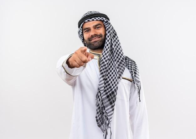 Arabische man in traditionele kleding lachend met blij gezicht wijzend met vinger staande over witte muur