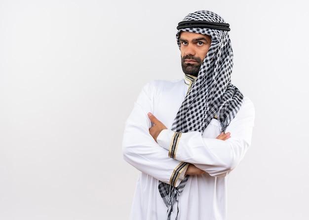 Arabische man in traditionele kleding met gekruiste armen op de borst opzij kijkend met ernstig gezicht staande over een witte muur