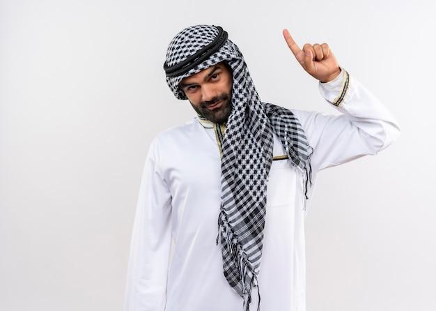 Arabische man in traditionele kleding met zelfverzekerde glimlach die met wijsvinger omhoog wijst die zich over witte muur bevindt