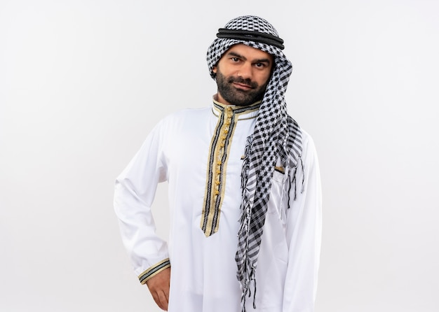 Arabische man in traditionele kleding met zelfverzekerde glimlach op gezicht staande over witte muur