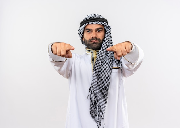 Arabische man in traditionele kleding op zoek zelfverzekerd wijzend met vingers staande over witte muur