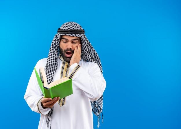 Arabische man in traditionele slijtage die in een boek kijkt geschokt staande over blauwe muur