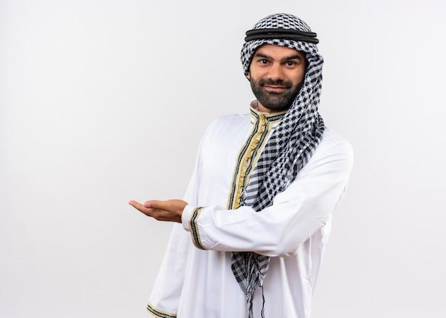 Arabische man in traditionele slijtage glimlachend prsenting met handarm staande over witte muur