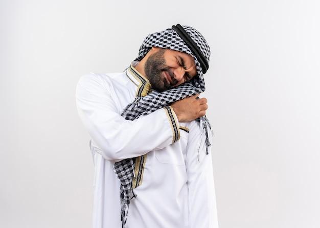 Arabische man in traditionele slijtage kijkt onwel schouder aanraken met pijn staande over witte muur