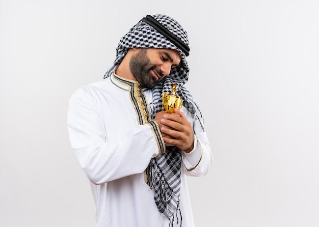 Arabische man in traditionele slijtage knuffelen zijn trofee glimlachend positieve emoties voelen staande over witte muur