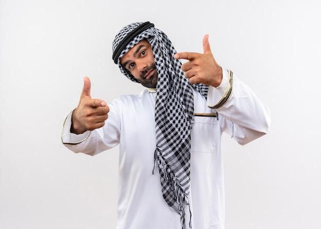 Arabische man in traditionele slijtage wijzend met vingers blij en positief staande over witte muur
