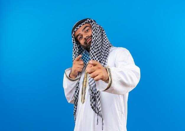 Arabische man in traditionele slijtage wijzend met vingers met zelfverzekerde glimlach op gezicht staande over blauwe muur