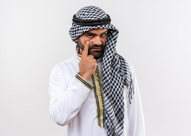Arabische man in traditionele slijtage wijzend naar zijn oog met zelfverzekerde uitdrukking staande over witte muur