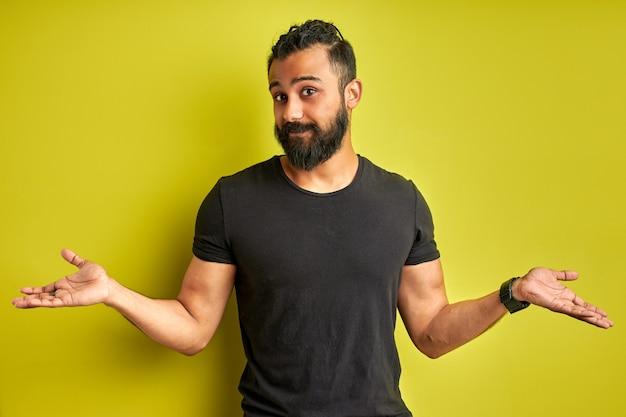 Arabische man kijkt bezorgd, bezorgd over de vraag, staat met gespreide armen, kijkt naar de camera, gefrustreerd