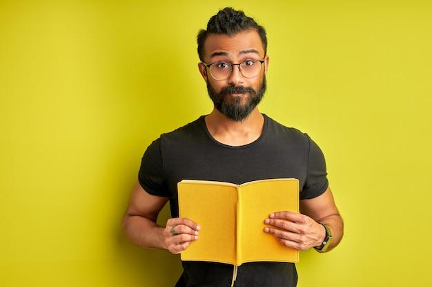 Arabische man met boek in handen poseren, jonge bebaarde man is klaar om te studeren