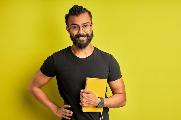 Arabische man met boek in handen, ruimdenkende mannelijke glimlach, geniet van onderwijs, studeren, geïsoleerde groene achtergrond