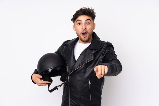 Arabische man met een motorhelm geïsoleerd op een witte muur verrast en wijst naar voren