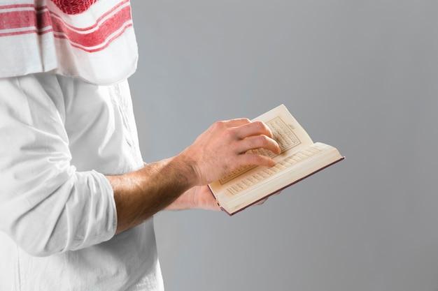 Arabische man met kandora koran houden