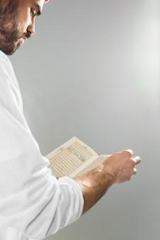 Arabische man met kandora lezen van koran