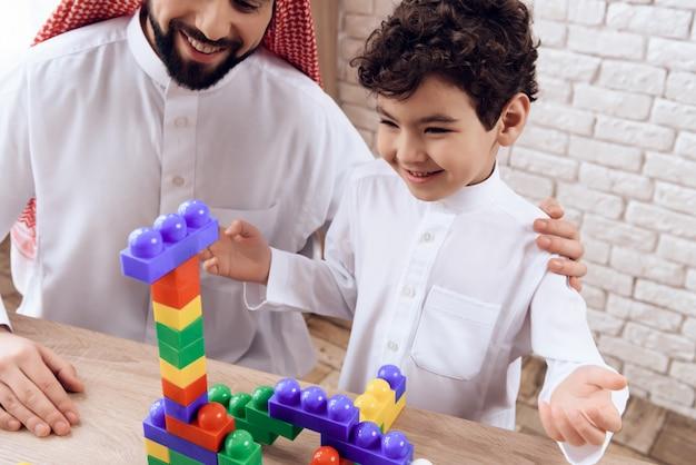 Arabische man met kleine jongen bouwt toren van plastic blokken.