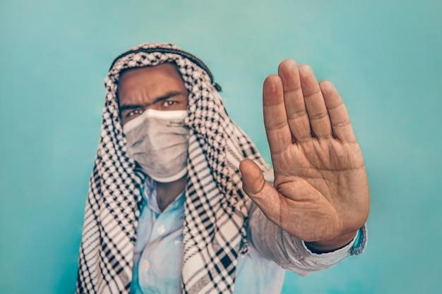 Arabische man met medisch gezichtsmasker met stopgebaar. mensen gezondheidszorg en geneeskunde concept. toegang zonder masker is verboden
