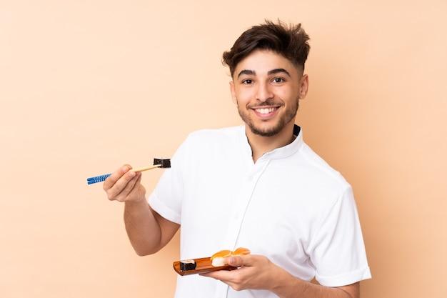 Arabische man sushi eten geïsoleerd op beige
