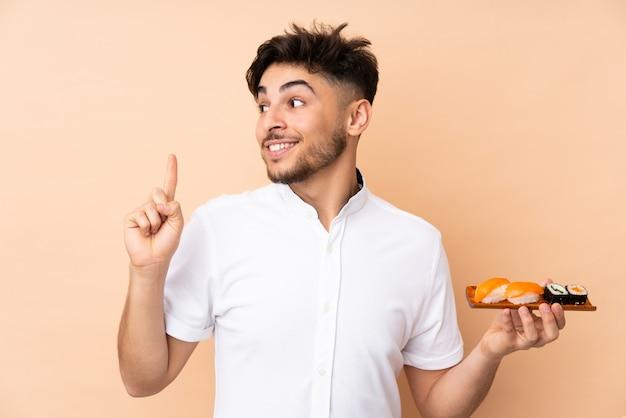 Arabische man sushi eten op beige muur met de bedoeling de oplossing te realiseren terwijl hij een vinger opheft