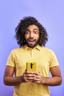 Arabische man wordt verrast na het lezen van bericht op smartphone, gekrulde mannelijke staan emotioneel reageren op bericht, camera kijken met geopende mond