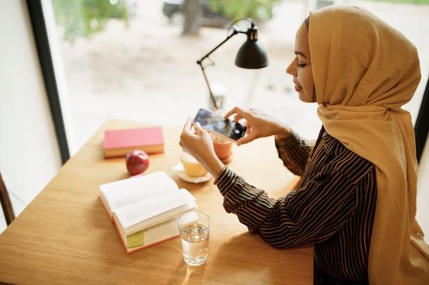 Arabische meisje maakt foto van kopje koffie in het universiteitscafé, bovenaanzicht. moslimvrouw met boeken die in bibliotheek zitten.
