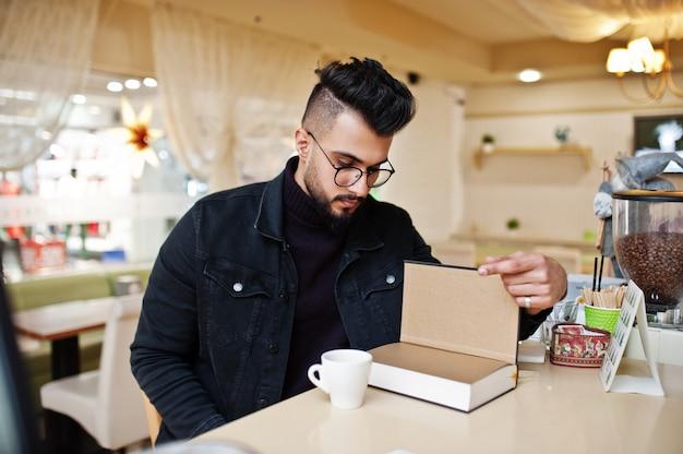 Arabische mens die op zwarte jeans en oogglazen dragen die in koffie zitten, boek lezen